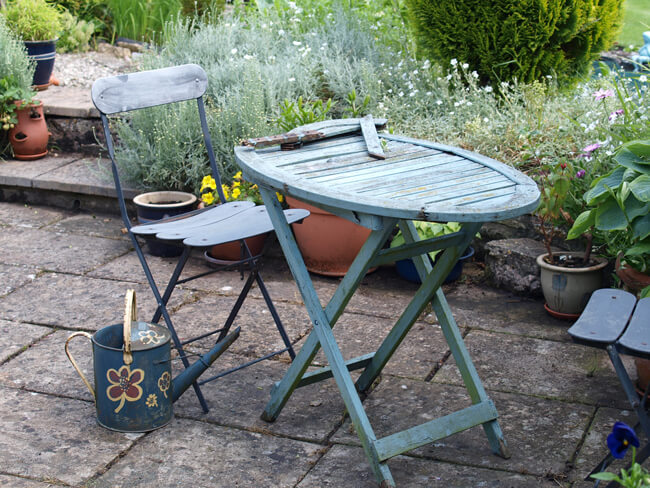 garden patio and furniture in need of cleaning and restoration